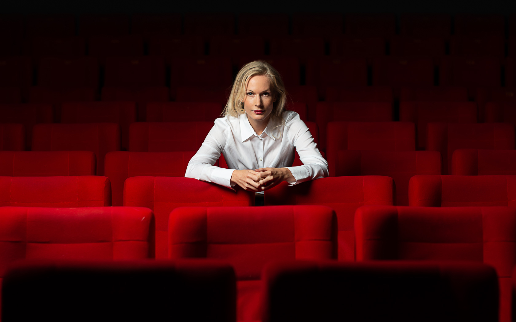Jennica in a red chair cinema - portrait and lifestyle photography